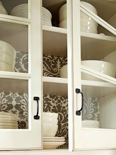 Cute DIY idea - add wallpaper or wrapping paper to a foam board at the back of cabinets.
