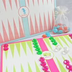 """BACKGAMMON SET...A colorful backgammon board that can be personalized with the icon, font and text of your choice. In four fabulous color combos with candy-colored game pieces and dice that resemble ice cubes, this is certainly a delectable take on a classic game, certain to make cocktail hour fun! Available in pink & green, coral & turquoise, navy & kelly and blue & brown [not shown].  Set includes glossy game board, plastic game pieces & crystal clear dice.  Board measures 9"""" x 12.5""""."""