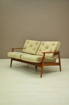 Teak zestiger jaren tweezitter. 1 zitkussen heeft wat kleine vlekjes, verkeert verder in een prima vintage staat.