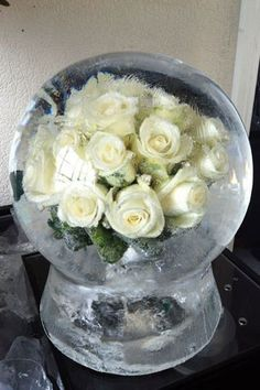 Not for the guest tables but maybe on a different one. A winter wedding centerpiece - roses in an ice globe! Or snowflakes!