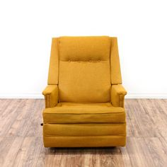 This rocking recliner chair is upholstered in a soft mustard fabric. This mid century modern style armchair has a button tufted back, comfortable seat cushion and footrest. Perfect for relaxing! #midcenturymodern #chairs #recliner #sandiegovintage #vintagefurniture