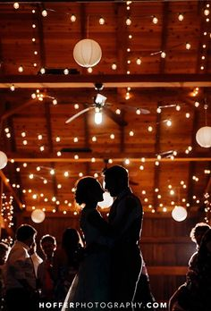 Bunting lights drape a high ceiling of wood beams in a scalloped fashion, creating an amber ambiance and romantic mood.