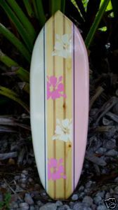 "1 Tropical Surf-Art Board    Measurement  24"" Long  7"" Wide  3/4"" Thick    This board has great details throughout.  The deck features twin cherry stained stripes along the center.    This board has an alternating pattern of pink and white on the rails.  There are pink and white hibiscus flowers embellishing the center deck.The center area is framed by thin black pinstripes."