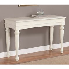 Spiff up your living area or entryway with this white sofa table. Constructed of solid wood and MDF with wood veneers, this table boasts a warm vanilla finish and ornate turned legs. The tables non-mar foot glides ensure your floor remains unscathed.