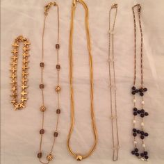 """Bundle of Neclaces and a Cross Bracelet Four 16"""" necklaces and a bracelet, all for only $25. The bracelet has crosses all around it & would be great on anyone, but especially if you're looking for a 1st Communion or Confirmation gift. One necklace has gold scrolled beads & brown transparent beads. Next is a beautiful shiny gold color with a single gold ball. Next has clear beads. The last has groupings of 3 wooden beads alternating with one white. Very feminine and dainty. 5 great looks that…"""