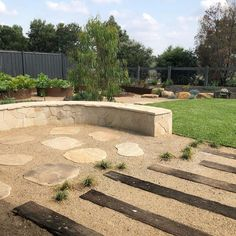 Curved sandstone garden seat, recycled timber set into granetic sand, just add a fire pit & enjoy.