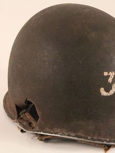 """Yeoman 2nd Class Fred Rucker was wearing this helmet when he died aboard LST 167 during the invasion of Vella Lavella, Solomon Islands in September 1943. The ship was attached by three Japanese dive bombers. One of them put two bombs into the ship and Ruckert and seven others were killed. The marking """"3""""50"""" on the helmet indicates Ruckert's battle station – the 3-inch, 50-caliber main deck gun. The helmet is  displayed in the Pacific gallery of The National WWII Museum."""
