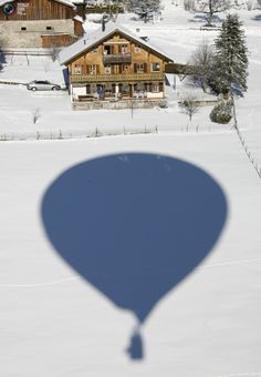 The shadow of a balloon is cast on the snow covered ground near a chalet at the International Hot Air Balloon Week in Chateau-d'Oex January 25, 2009. Over 80 balloons from 20 countries are participating in the ballooning event in the Swiss mountain resort famous for ideal flight conditions due to an exceptional microclimate. REUTERS/Denis Balibouse