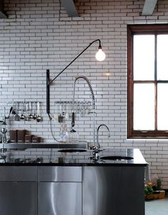 Source: Dane Tashima Subway tiles, stainless steel and a swing arm wall light. That Swing arm is called a Potence Lamp designed by Jean Prouvé back in the You can find it at stores like Skandium. New Kitchen, Kitchen Decor, Kitchen Tiles, Kitchen Brick, Loft Kitchen, Kitchen White, Kitchen Cabinets, Industrial Interiors, Industrial Design