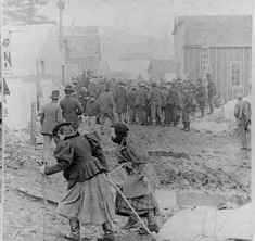 Women pulling a sled loaded with provisions through the streets of Skagway, Alaska in 1898.  Photograph courtesy of David Sundman.