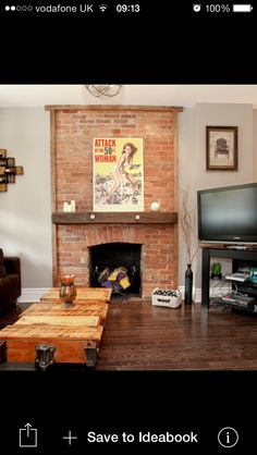 Exposed brick fireplace with wooden mantel. This looks brilliant. Get DK on to it