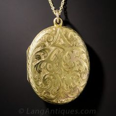 A classic Victorian oval pendant locket from late-nineteenth/early-twentieth century Great Britain, beautifully crafted in 15ct. yellow gold, intricately and ornately hand-engraved on both sides. Superb. 1 1/2 by 1 inch. Small fanciful monogram 'MW' can probably be polished off if so desired. The gold chain is new.