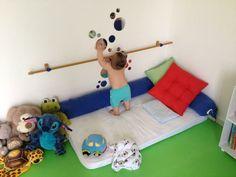 Os espelhos são peças fundamentais no quarto montessoriano. Ressalto que, o ideal é que eles sejam de acrílico, por serem mais seguros. Nesse modelo de quarto, a cama fica no chão, nesse caso, um colchão. A barra faz parte para trazer mobilidade à criança.