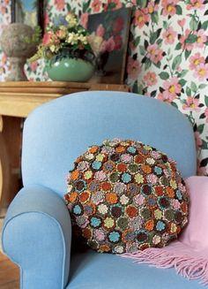un coussin réalisé avec plein de fleurs en croche de toutes les couleurs cousues sur un fond en lin rond comme housse, posé sur un fauteuil ...