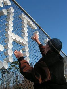Hundreds of styrofoam cups are transformed into typography when arranged in a chain-link fence. Diy Fence, Fence Art, Fence Ideas, Yard Fencing, Cup Design, Sign Design, Fence Weaving, Styrofoam Art, Fence Signs