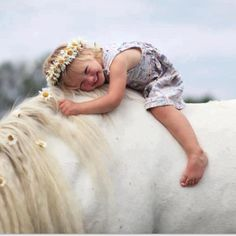Adorable little girl and her horse with flowers