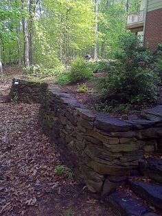 Drystacked Stone Wall and Steps - The client wanted a level area behind their house that is atop a steep wooded hill. We built this 77' long wall using Pennsylv…