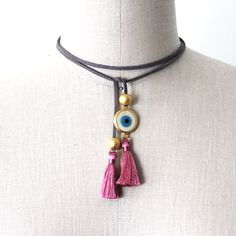 "Our latest creation ""Suede Evil Eye Choker"" is a trendy piece that can be worn many different ways. It can be a chocker, a necklace or even a bracelet. One size fits all with a simple tie or bow. It is made of a grey suede ribbon, a 24K gold plated evil eye and round beads and a soft pink silk tassel. Shop all our Persian jewelry online at alangoo.com/spenta-armaiti"