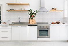 cuisine blanche linéaire aménagée avec des armoires blanches, étagères en bois et crédence en carreaux métro blancs