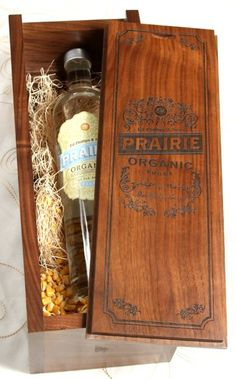 This custom wooden box was designed to showcase Prairie Organic Vodka. The laser engraved slide-off lid reveals the liquor bottle, nestled in corn kernels and straw, which highlights the organic ingredients of the beverage. Truly a unforgettable impression!