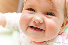 Portrait of a cute baby girl smiling, showing her first teeth.