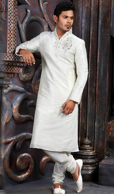 Off White Poly Dupion Silk Kurta with Pyjama Become the object of everyone's attention donning into this off white poly dupion silk kurta pyjama. Collar and neckline flaunt bugle beads and crystals enhanced decorative patterns. Embellished paisley motif on the chest contributes to the elegance of the kurta. Comes with matching bottom. #SherwaniOnlineShopping #LatestWeddingSherwani