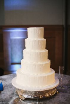 All white brides cake with dots - Photo by Sara & Rocky Photography