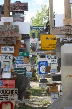 """Signpost Forest, Watson Lake, Yukon.  See if you can locate a Florida license plate, the date """"July 2011,""""  a handicapped symbol, and """"Wicks.""""  06/2013."""