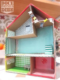 cardboard dollhouse with scrapbook paper for wallpaper - a fun rainy day craft for kids
