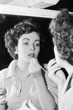 Elizabeth Taylor touching up her lipstick, 1950, photo by Davis Boulton