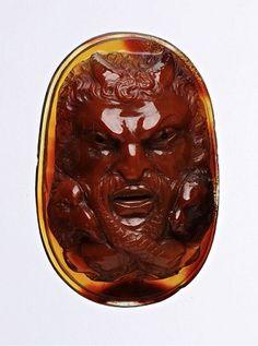 Camee. Masker, 17e eeuw. Agaat, roodbruine kleur. 39 x 26 mm, D. 12 mm, gew. 13,65 gr. Masker frontaal met horens in haar; links kop van een adelaar; rechts kop van een leeuw; slang met 2 koppen onder kin, lijf gekruld om mond als snor. -Rijksmuseum van Oudheden, Leiden-