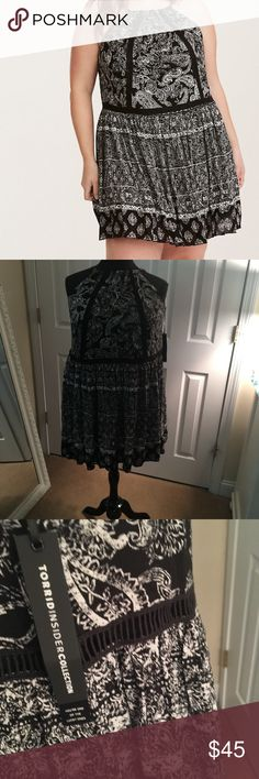 """Torrid Insider Paisley Print Trapeze Dress 0X New with tags Torrid Insider Paisley Print Gauze Trapeze Dress, size 0 (0X).  Shown on a 2X dress form!  This is a #nofilterneeded festival style. Black gauze has free spirit feels with a lightweight trapeze construction. The swirling white paisley print matches your grooving, along with an adjustable halter tie neck. The keyhole cutout is boho chic with embellished tassels. Crochet insets detail the drop-down waist and back.  ~39"""" from shoulder…"""