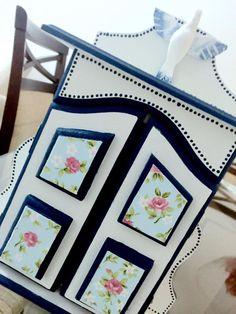 Detalhe oratório pintando em branco e azul, revestido de tecido floral.