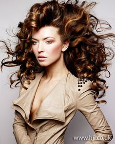 Big Curls!  Long brunette hair was prepped with mousse and roughly blow-dried to add volume and texture. Once dry, hair was tonged in small sections to create tight curls. Hair was then smoothed throughout with serum to create glossy ringlets.