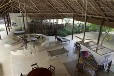 The huge makuti roof covers a platform which is also done in free form, and from that platform, different cube-shaped, coral stone buildings representing private ...