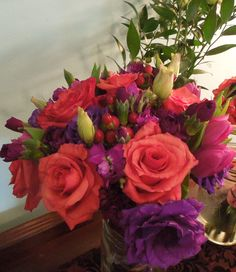 Coral roses, purple lisianthus, purple delphinium bouquet.