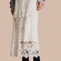 A panelled skirt formed from ornately embroidered tulle with scalloped tiers to accentuate its femininity. The silk lining is cut to graze the delicate floral lace at the hem.