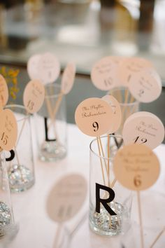 a modern take on the seating chart - names on a stick placed in corresponding letter glasses |  Photography by dlweddings.com  Read more - http://www.stylemepretty.com/2013/09/06/new-york-city-wedding-from-divine-light-photography/