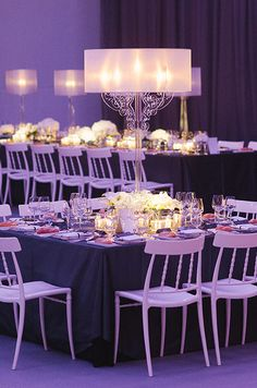 A square table is punctuated with a single large candelabra and tons of votives.