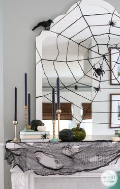 Love this modern halloween mantle with it's spider web mirror, ravens and gold candle sticks.