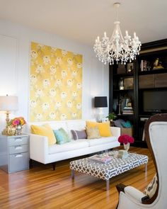 wallpaper as art, file cabinet as side table, upholstered coffee table, build in bookshelf, and beautiful chandelier- whats not to love about this room!?