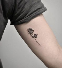 Single needle rose tattoo on the left inner arm.