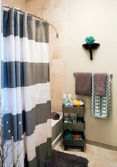 contemporary bathroom by Dona Rosene Interiors...Rosene completely outfitted the bathroom, right down to the toilet paper. A dotted towel from Home Goods continues the bedroom's teal and gray color scheme. She picked up the shower curtain at West Elm and the cart at Cost Plus World Market. Bath mat: Home Goods