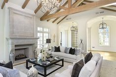 Chic white living room features a vaulted truss ceiling over white sofas and chairs adorned with gray and black pillows facing a black coffee table with glass top alongside a gray limestone fireplace.