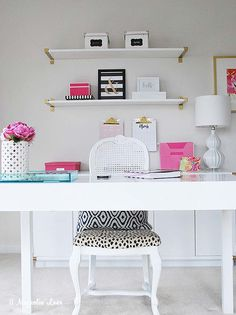 White furniture doesn't have to look boring! Pair a streamlined desk from HomeGoods with fun and bright accessories. This feminine office is a fun spot to work from home or handle home organization. Gold clipboards hang on the wall to keep schedules at hand and lots of storage keeps everything organized. Sponsored Pin.