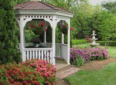 weiße Gartenlaube Rosen Brunnen englischer Garten