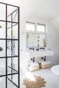 black steel framed shower glass, black matte faucets, round seagrass rug.