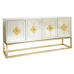 Reflectology.Minimalist forms meet Maximalist glamour. Antiqued glass with a polished brass base. Two double-door compartments open to reveal a bright robin's egg blue interior fitted with two adjustable shelves. Quatrefoil handles and escutcheons add a decorative flourish to the simple form. Use our reflective Delphine Credenza as a buffet in your dining room, place it behind your sofa as a chic console, or give your foyer the gift of glamour.Discover the entire Delphine Collection.