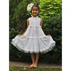 A beautiful feminine flowing eyelet dress from Kid Cute Ture! This white eyelet dress is sleeveless with rows of ruffles across the henley style button up chest and a ruffle trimmed neckline. It features an empire waist with a double layer of soft eyelet