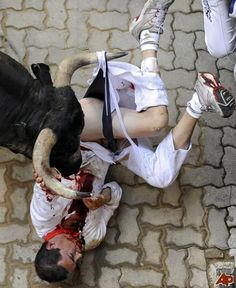 A reveler is gored during the fourth Running of the Bulls in Spain